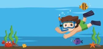 Um mergulho do rapaz pequeno com os peixes sob o oceano Imagens de Stock