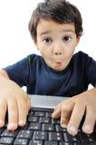 Um miúdo bonito pequeno com um portátil isolado, surpresa Fotos de Stock