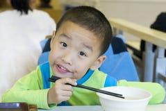 Um miúdo chinês tem o pequeno almoço Imagens de Stock Royalty Free