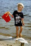 Um miúdo com a cubeta Foto de Stock Royalty Free