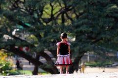 Um miúdo pequeno de india no jardim com pensamento profundo Foto de Stock