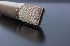 Um microfone que reflete fora de uma superfície brilhante Foto de Stock