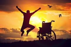 Um milagre aconteceu Desabilitou o homem deficiente é saudável outra vez É feliz e saltando no por do sol fotos de stock