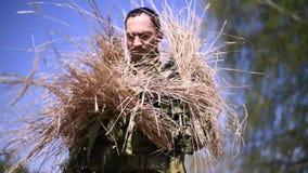 Um militar é camuflado fora pondo sobre uma rede da camuflagem com a grama seca que cola fora dela filme