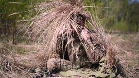 Um militar ? camuflado fora pondo sobre uma rede da camuflagem com a grama seca que cola fora dela filme