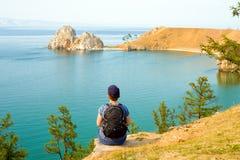 Um mochileiro da mulher olha a rocha de Shamanka, cabo Burhan na ilha de Olkhon Lago Baikal, Rússia fotografia de stock royalty free