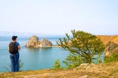 Um mochileiro da mulher olha a rocha de Shamanka, cabo Burhan na ilha de Olkhon Lago Baikal, Rússia imagens de stock royalty free
