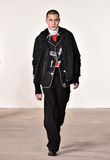 Um modelo anda a pista de decolagem no desfile de moda de Tim Coppens durante a queda dos homens da semana de moda de New York/in Imagens de Stock Royalty Free