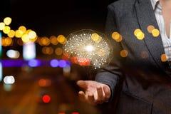 Um modelo digital do cérebro humano está pendurando acima da mão de uma mulher de negócios no fundo das luzes da noite fotos de stock