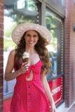 Um modelo moreno bonito Eats Ice Cream fora de uma loja de gelado imagem de stock