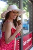 Um modelo moreno bonito Eats Ice Cream fora de uma loja de gelado imagens de stock royalty free