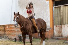 Um modelo moreno latino-americano bonito Rides um cavalo em uma exploração agrícola mexicana imagens de stock royalty free