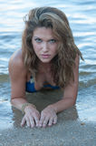 Um modelo na praia no short da sarja de Nimes e na parte superior de biquini azul foto de stock