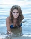 Um modelo na praia no short da sarja de Nimes e na parte superior de biquini azul imagem de stock