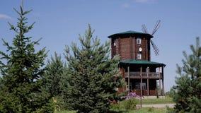 Um moinho de madeira bonito do log está entre as árvores Campo bonito Planta geral video estoque