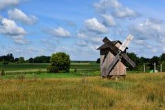 Um moinho de vento de madeira abandonado no campo verde vasto perto dos celeiros da floresta e outras construções estão em seguid imagens de stock royalty free