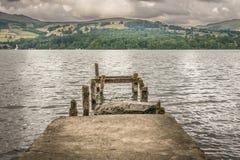 Um molhe de pedra temporário em um lago, em montanhas e em nuvens de tempestade fotos de stock