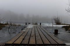Um molhe e um lago congelado na névoa Imagem de Stock Royalty Free