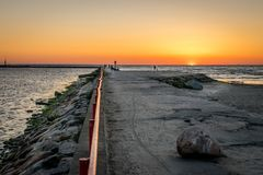 Um molhe ou um cais com povos mostrados em silhueta com um por do sol no mar fotos de stock