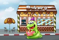 Um monstro com um bolo perto da padaria Fotos de Stock Royalty Free
