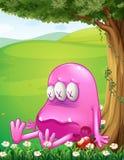 Um monstro cor-de-rosa cansado ao lado de uma árvore Fotografia de Stock Royalty Free
