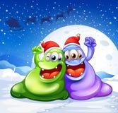 Um monstro verde e violeta que veste um chapéu vermelho para o Natal Imagens de Stock Royalty Free