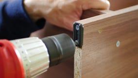 Um montador bem sucedido da mobília usa uma chave de fenda para montar uma prateleira, close-up video estoque