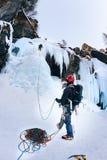Um montanhista amarra o líder durante uma escalada do gelo Imagem de Stock