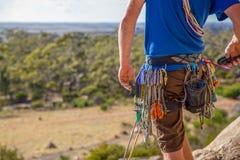 Um montanhista de rocha verifica seus engrenagem e rádio antes de escalar fotografia de stock royalty free
