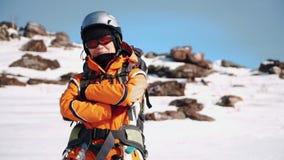 Um montanhista em suportes do equipamento em um monte nevado e com cruzado cruza seus braços sobre sua caixa filme