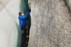Um montanhista livre sem seguro com os dois machados de gelo aumenta de uma quebra na geleira Escalada livre sem cordas imagem de stock royalty free