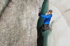 Um montanhista livre sem seguro com os dois machados de gelo aumenta de uma quebra na geleira Escalada livre sem cordas fotografia de stock royalty free