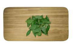 Um monte de folhas do louro do prurido em uma placa de corte isolada fotografia de stock