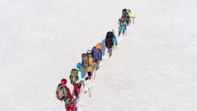 Um monte grande coberto com a neve que tenta knee-deep obter um grupo de alpinistas treinados, s?o as tra??es profundas e confiam video estoque