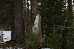 Um monumento velho abandonado com uma estrela vermelha que encontra-se entre as árvores fotos de stock