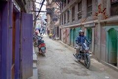 Um motociclista em uma rua alinhada com portas coloridas imagens de stock royalty free