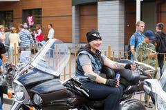 Um motociclista fêmea está sentando-se em uma motocicleta com uma Bull vermelha pode e um cigarro eletrônico imagens de stock royalty free
