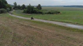 Um motociclista novo em um terno protetor e em um capacete pretos que executam a condução com o deslizamento da roda traseira em  filme