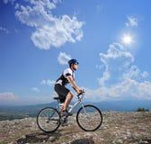Um motociclista novo que biking uma bicicleta de montanha Imagem de Stock