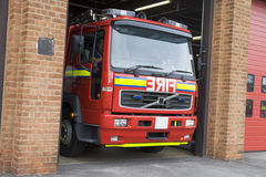 Um motor de incêndio que sae da estação de incêndio Fotografia de Stock