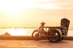 Um motorcicle do side-car perto do mar com por do sol fotos de stock