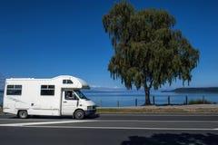 Um motorhome que conduz ao longo da costa do lago Taupo na ilha norte de Nova Zelândia fotografia de stock royalty free