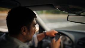 Um motorista masculino que texting em um telefone celular ao conduzir video estoque