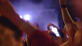 Um movimento lento de uma multidão de fãs em um concerto da música da noite video estoque