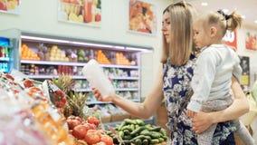 Um mum com filha pequena escolhe produtos no mercado grande filme