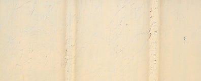 Um muro de cimento velho, rachado, com uma superfície lascada, pintada na cor bege fotos de stock royalty free