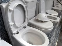 Um número de bacias de toalete brancas na loja e no capacete branco da construção imagem de stock royalty free