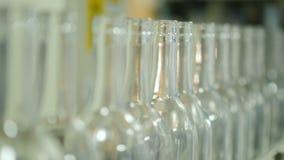 Um número de garrafas vazias para bebidas alcoólicas no transporte Mova-se lentamente ao longo da fita video estoque