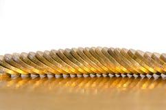 Um número de moedas que encontram-se na superfície dourada foto de stock royalty free