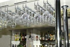 Um número de vidros lavados penduraram para secar na barra Imagem de Stock Royalty Free